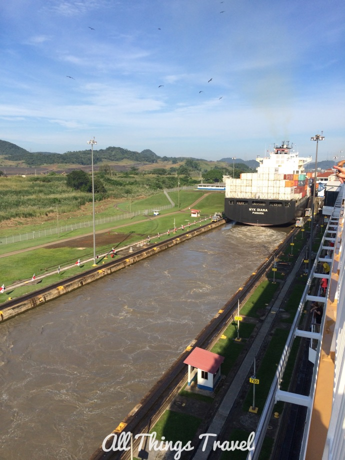"Container ship in the lock next to us with ""mules"" to the right of the ship  on the track"